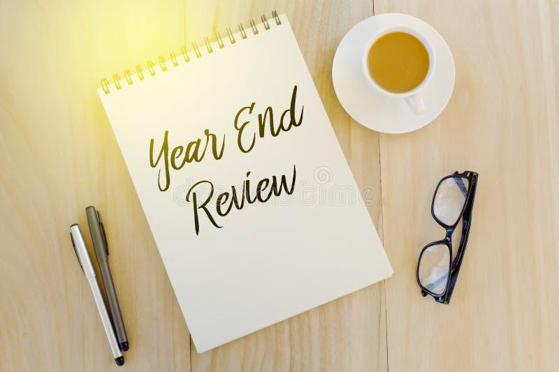 Vista superior da pena, dos óculos de sol, de uma xícara de café e do caderno escritos com revisão do final do ano no fundo de ma foto de stock