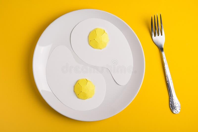 Vista superior da placa branca com os ovos fritos de papel no fundo de papel amarelo Bom dia ou arte do alimento fotografia de stock