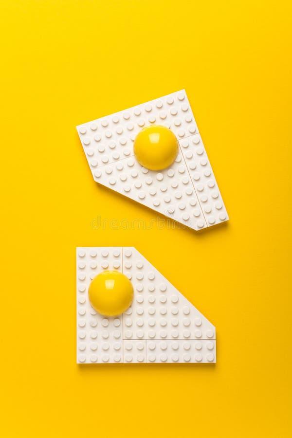 Vista superior da placa branca com os ovos fritos do desenhista do ` s das crianças no fundo de papel amarelo Conceito do bom dia foto de stock royalty free