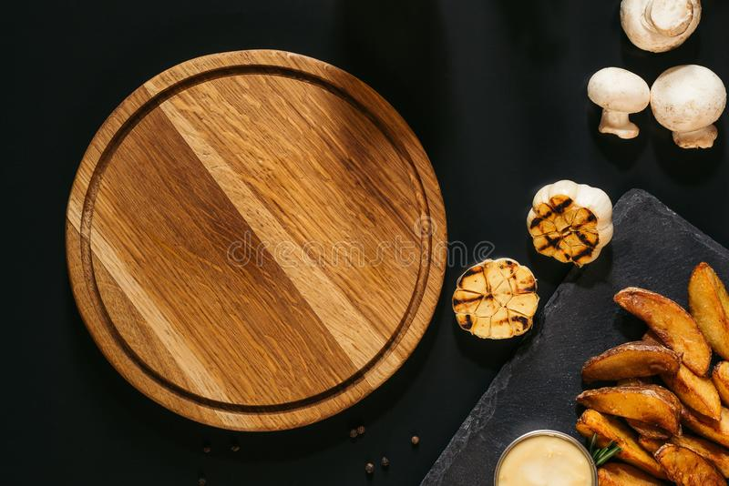 vista superior da placa de madeira vazia, do alho grelhado, dos cogumelos e de batatas cozidas com molho fotos de stock royalty free