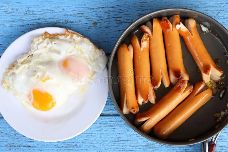 Vista superior da refeição do café da manhã, de salsichas fritadas na bandeja preta e de ovos fritos no prato branco na tabela de fotos de stock