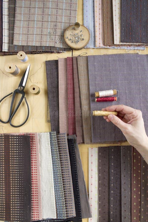 Vista superior da tabela da costura com telas, fontes para a decoração home ou projeto e mão estofando do ` s da mulher fotos de stock