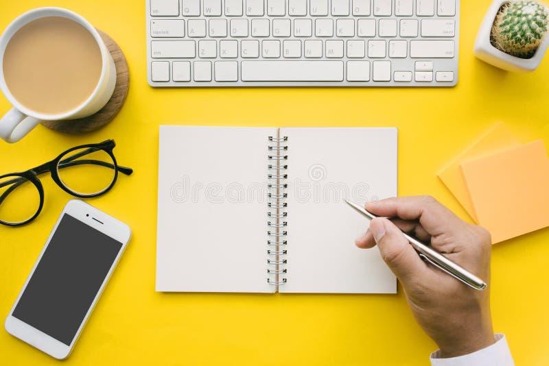 Vista superior da tabela da mesa de escritório com mão masculina no bloco de notas imagem de stock