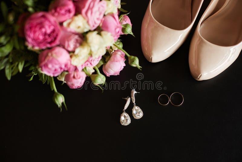 Vista superior das alianças de casamento, dos brincos, do ramalhete bonito de flores cor-de-rosa e de sapatas fêmeas no fundo pre fotos de stock royalty free