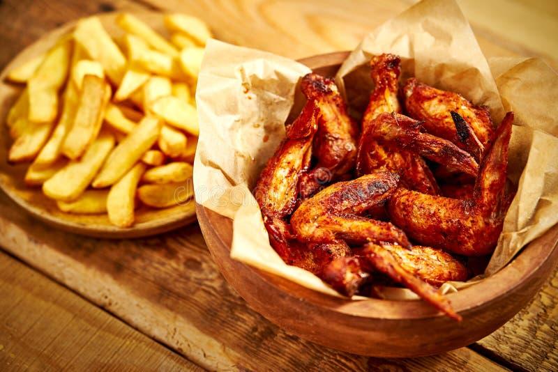 Vista superior das asas e de batatas fritas deliciosas de frango frito na tabela de madeira imagem de stock