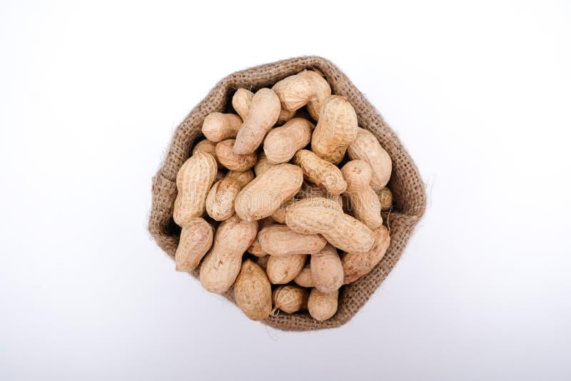 A vista superior de amendoins crus isolados no saco do saco do buralap, fecha-se acima da foto do amendoim imagens de stock royalty free