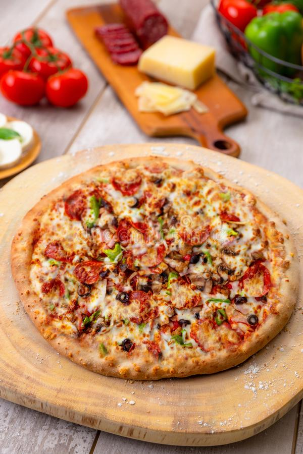 Vista superior de arriba vertical de la pizza suprema entera, de las verduras cocidas frescas y de las carnes fotos de archivo libres de regalías