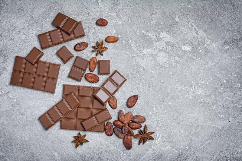 A vista superior de barras de chocolate quebradas com feijões e anis de cacau protagoniza como o ingrediente para confeitos fotos de stock royalty free