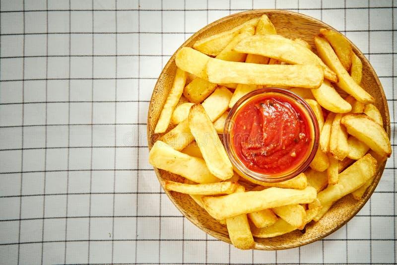 Vista superior de batatas fritas deliciosas na placa com molho na toalha de mesa quadriculado imagens de stock