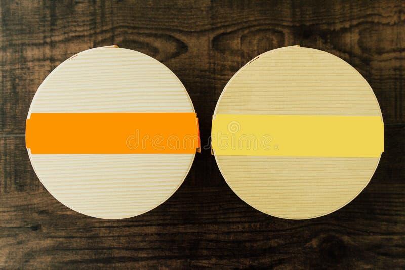 Vista superior de caixas de madeira do círculo com a faixa amarela e alaranjada da cor no fundo de madeira da textura Para a refe fotografia de stock
