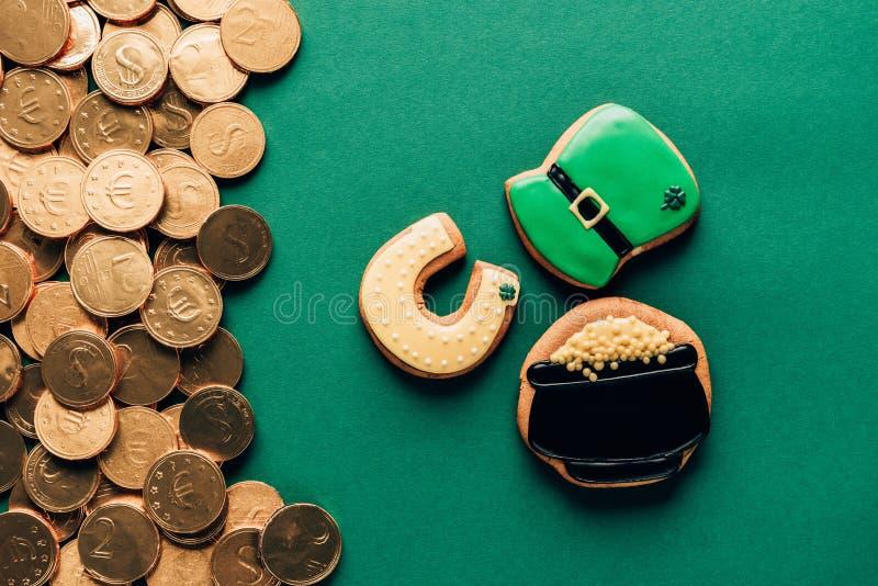 vista superior de cookies da crosta de gelo e de moedas douradas no verde, patricks do st fotografia de stock