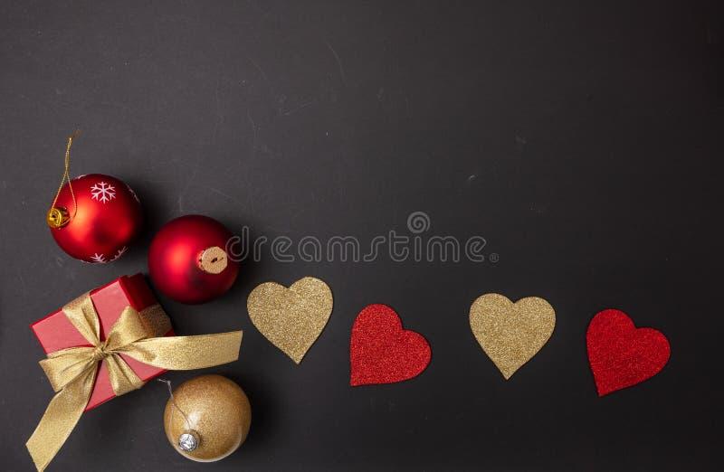 Vista superior de corazones rojos y de oro, de una caja de regalo con la cinta roja y de una bola de la Navidad, fondo negro imagen de archivo
