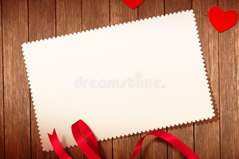 Vista superior de corazones y de la cinta rojos decorativos con la tarjeta de felicitación en el viejo fondo de madera, concepto  fotos de archivo