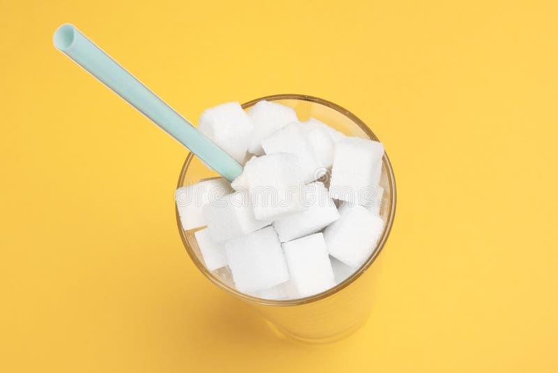 Vista superior de cubos do açúcar Um vidro claro enchido com os cubos do açúcar em um fundo amarelo Da cor fotografia m?nima da v imagens de stock