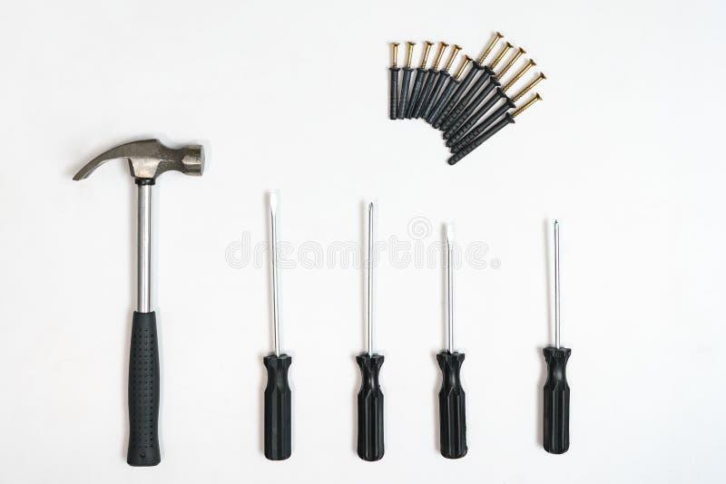 Vista superior de destornilladores, martillo, tornillos, pasadores en el contexto blanco fotos de archivo