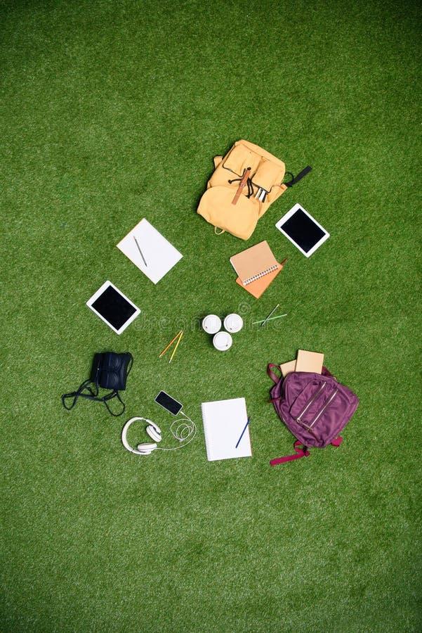 vista superior de dispositivos, de mochilas y de cuadernos digitales dispuestos foto de archivo