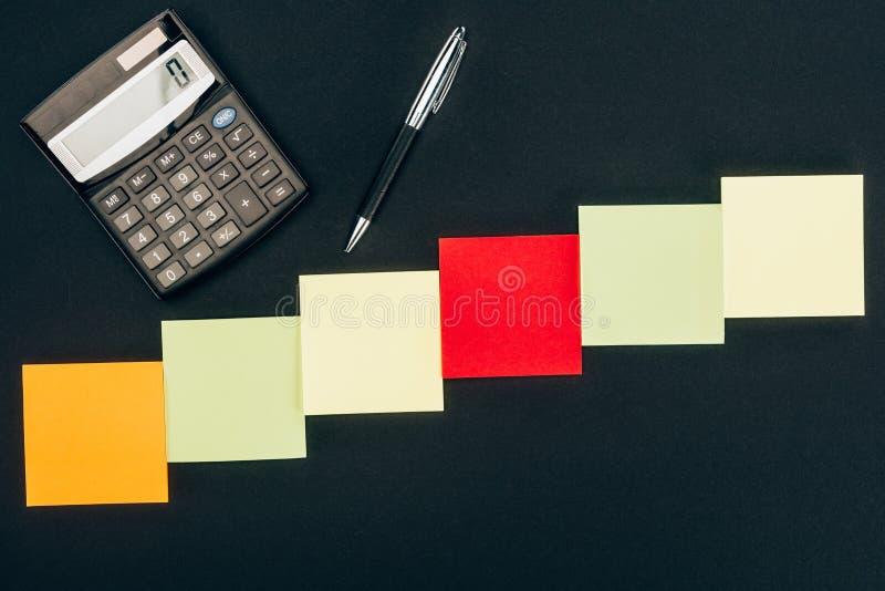 vista superior de diversas notas, calculadora y pluma en blanco imagenes de archivo