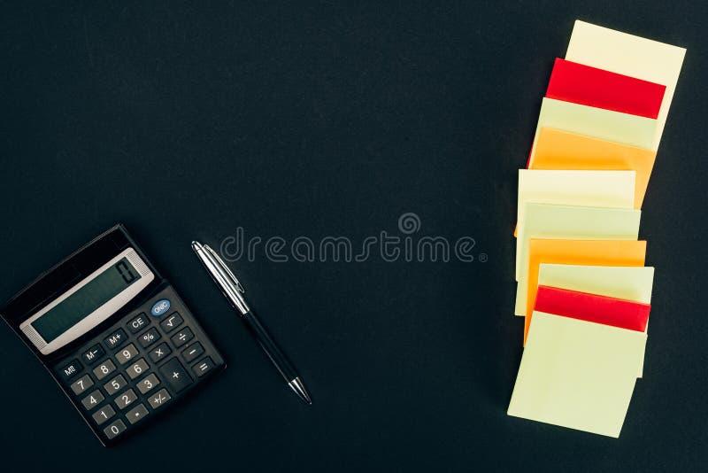 vista superior de diversas notas, calculadora y pluma en blanco coloridas foto de archivo libre de regalías