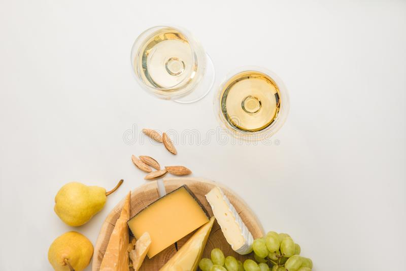 Vista superior de diversos tipos de queso en el tablero de madera, las copas de vino, la almendra y las frutas en blanco fotografía de archivo