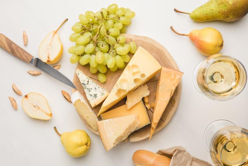 Vista superior de diversos tipos de queso en el tablero de madera rodeado por el cuchillo, las frutas, la almendra, el baguette y imagen de archivo libre de regalías