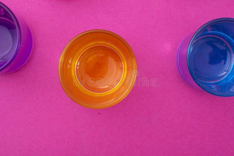 Vista superior de diversos vidrios del color en fondo púrpura foto de archivo libre de regalías