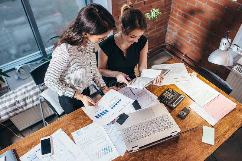 Vista superior de dois colegas e mesas fêmeas cobertos com os papéis e os originais Mulheres de negócios que estudam os dados que fotografia de stock