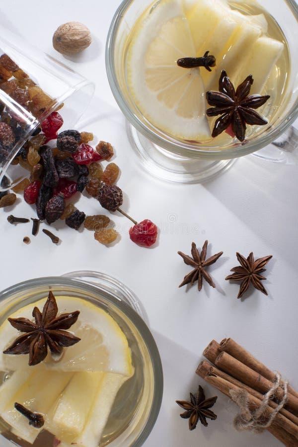 Vista superior de dos vasos con vino blanco asado con una manzana cortada, un trozo de limón y anís, un frasco de fruta seca roci foto de archivo