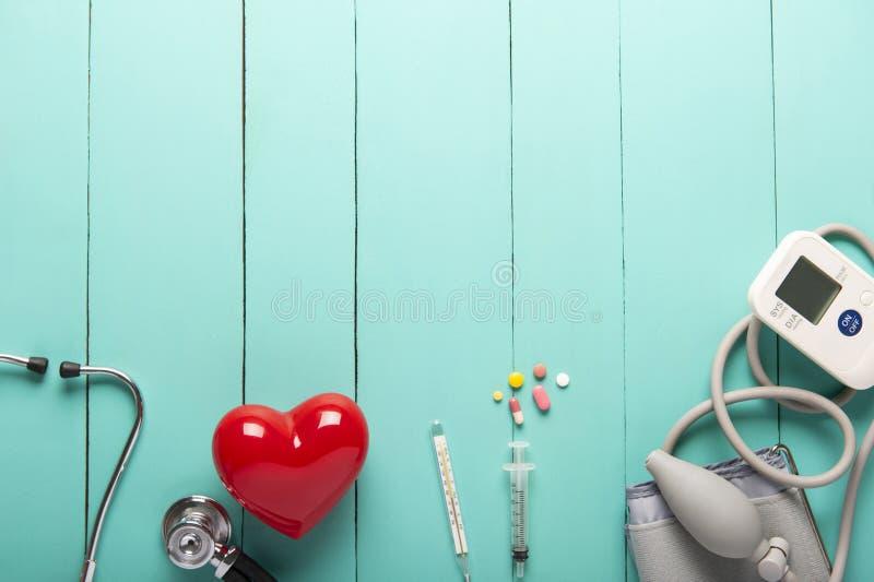 Vista superior de estetoscopios, corazón rojo plástico, monitor y drogas portátiles automáticos de la presión arterial o del ritm imágenes de archivo libres de regalías