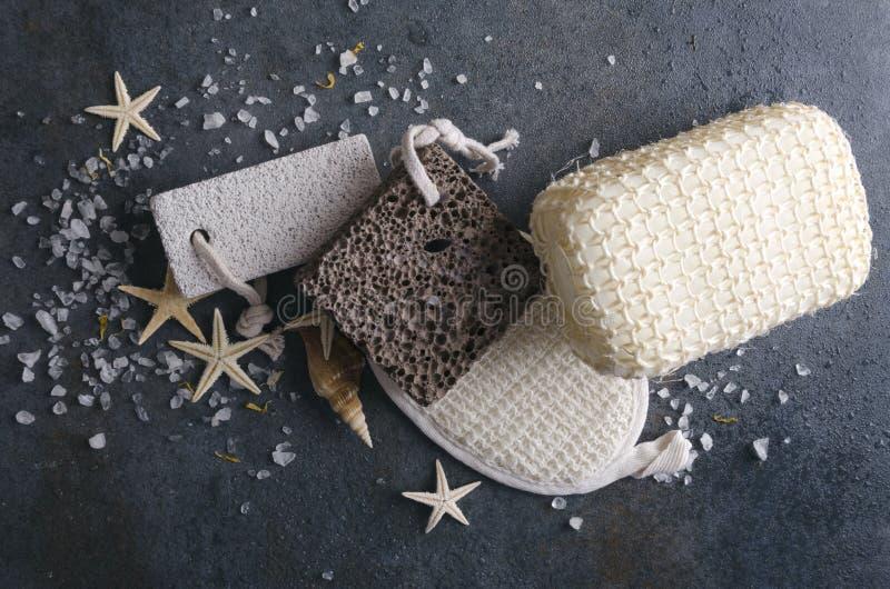 Vista superior de ferramentas do banho, sal do mar, estrelas do mar na superfície cinzenta rústica Polimento, esponjas do eco imagem de stock
