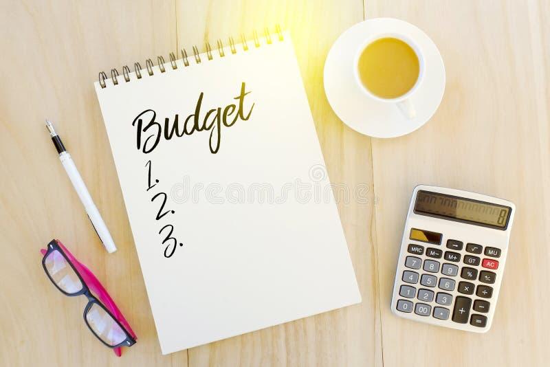 Vista superior de gafas de sol, de la pluma, de la calculadora, de una taza de café y de cuaderno escritos con el presupuesto y d foto de archivo libre de regalías