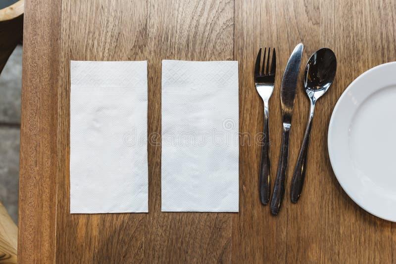Vista superior de guardanapo e de cutelaria do tecido sobre a tabela de madeira Para a bandeira do alimento fotos de stock