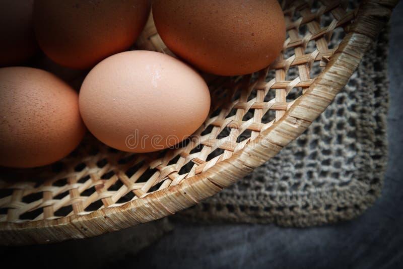 Vista superior de huevos en una cesta de la paja en servilletas de lino naturales y un fondo de madera rústico fotografía de archivo