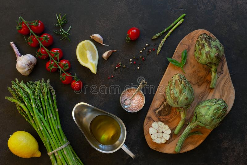 Vista superior de la alcachofa fresca y manojo de espárrago verde con aceite de oliva, los tomates, el limón y el ajo en la tabla foto de archivo libre de regalías