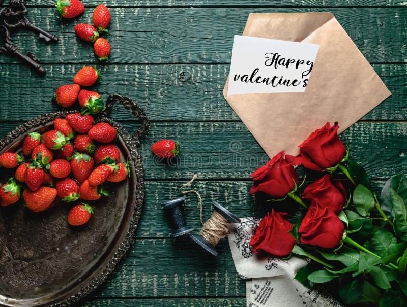 vista superior de la bandeja del vintage, de rosas rojas y del sobre con la tarjeta feliz del día de tarjetas del día de San Vale foto de archivo libre de regalías
