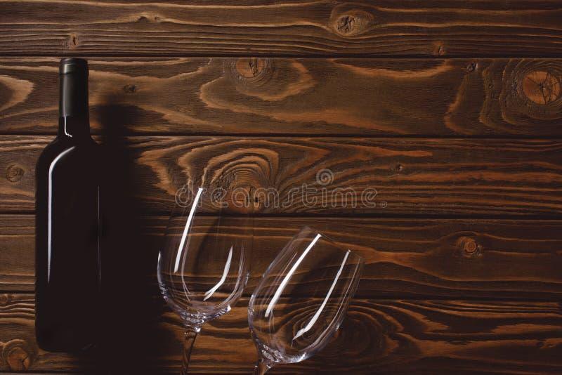 vista superior de la botella de vino tinto con los vidrios vacíos foto de archivo
