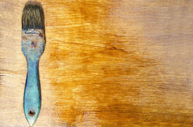 Vista superior de la brocha rústica en la superficie de madera barnizada fotos de archivo