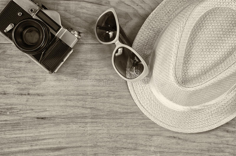 Vista superior de la cámara vieja del sombrero de las gafas de sol elegantes de la mujer sobre la tabla de madera Foto blanco y n foto de archivo libre de regalías