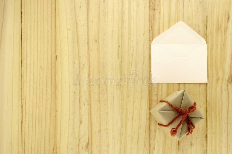 Vista superior de la caja de regalo del arte con el sobre en la madera fotografía de archivo