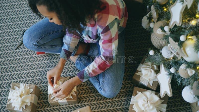 Vista superior de la caja de regalo atractiva del embalaje de la muchacha de la raza mixta cerca del árbol de navidad en casa fotos de archivo