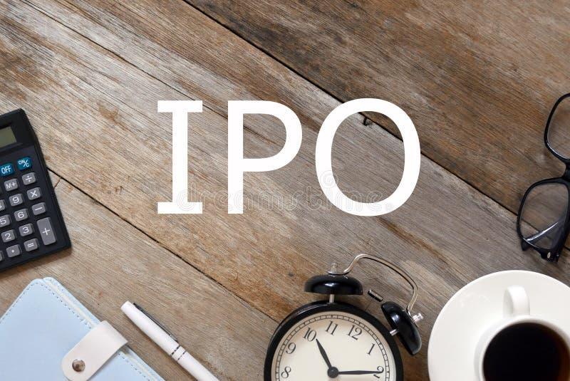 Vista superior de la calculadora, cuaderno, pluma, reloj, una taza del café, gafas de sol en el fondo de madera escrito con IPO fotografía de archivo