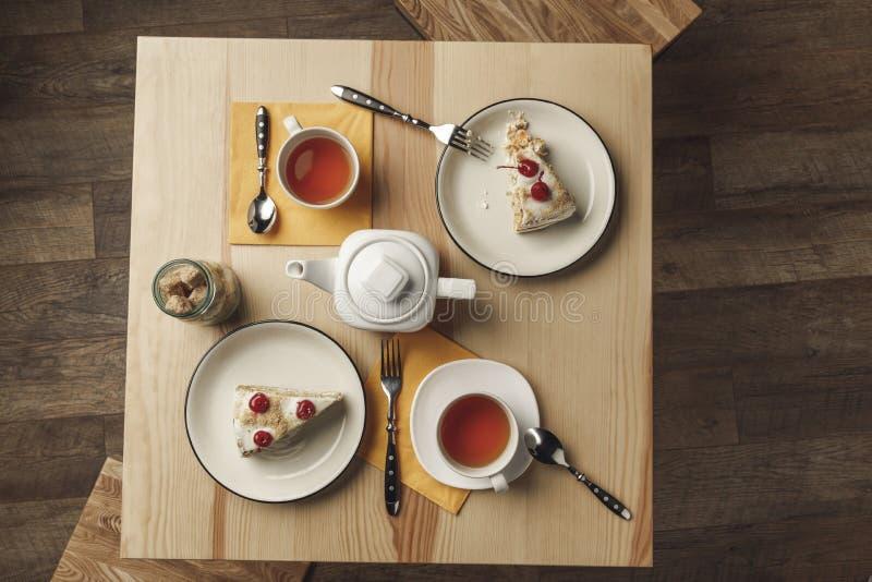vista superior de la caldera, de dos tazas con té caliente y de pasteles deliciosos imagenes de archivo
