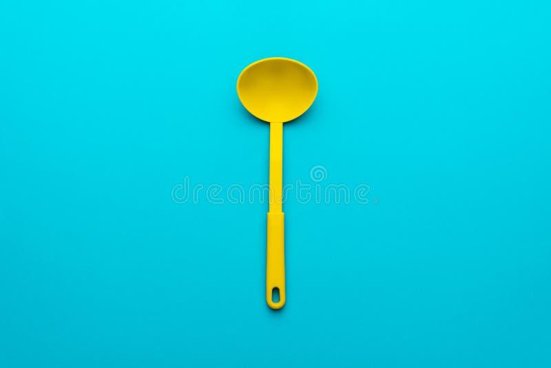 Vista superior de la cucharón plástica amarilla sobre fondo de los azules turquesa con el espacio de la copia imagenes de archivo