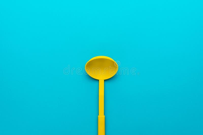Vista superior de la cucharón plástica amarilla sobre fondo de los azules turquesa con el espacio de la copia imagen de archivo libre de regalías