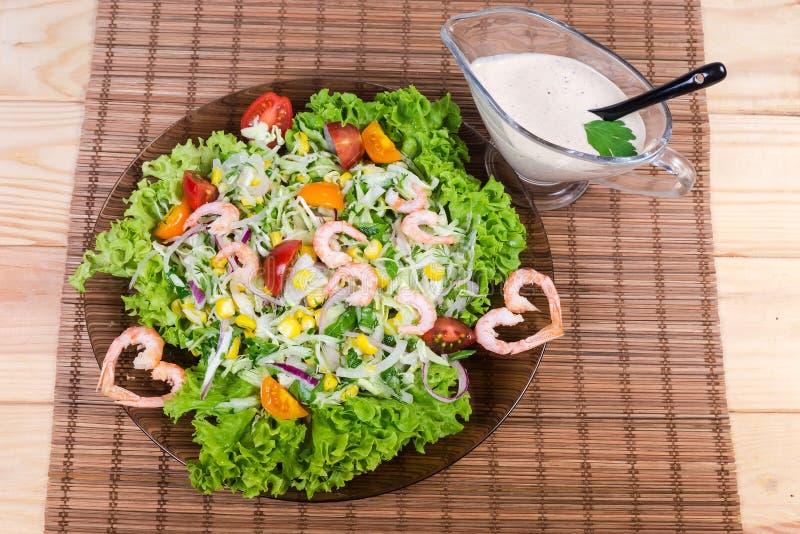 Vista superior de la ensalada vegetal con las colas del camarón, salsa blanca fotos de archivo