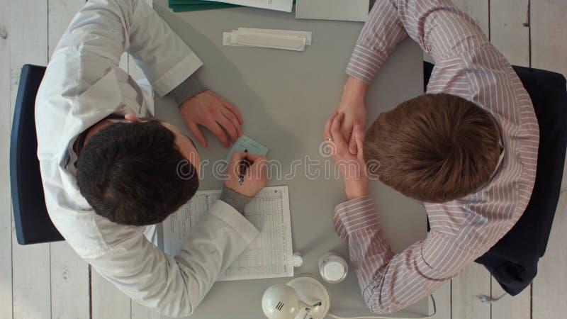 Vista superior de la escritura del doctor en una carta médica con el paciente foto de archivo