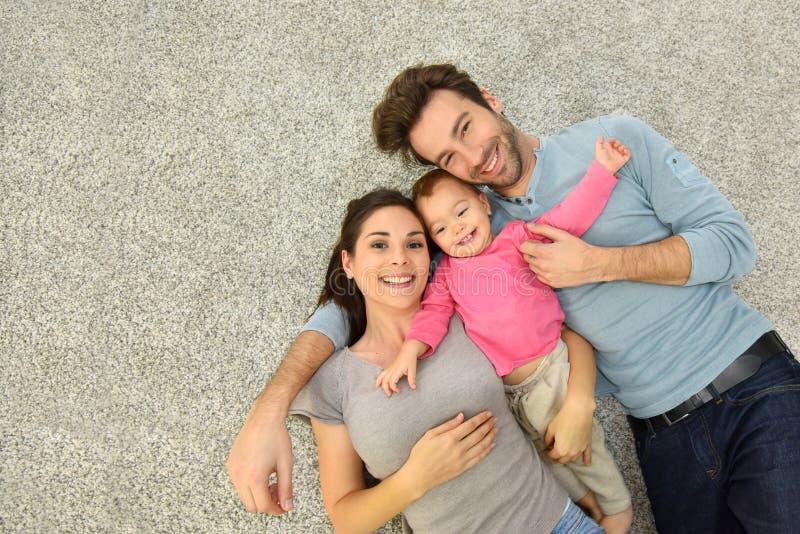 Vista superior de la familia de tres que ponen en moqueta foto de archivo libre de regalías