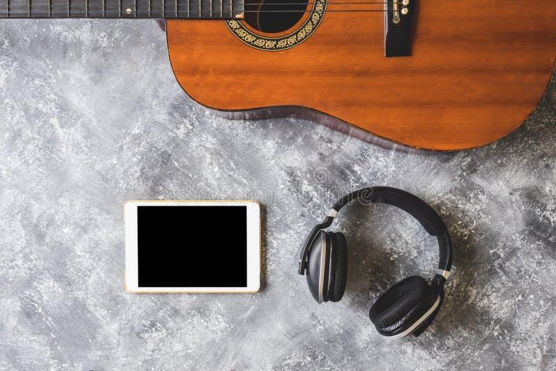 Vista superior de la guitarra con el auricular y la tableta en fondo del grunge foto de archivo libre de regalías