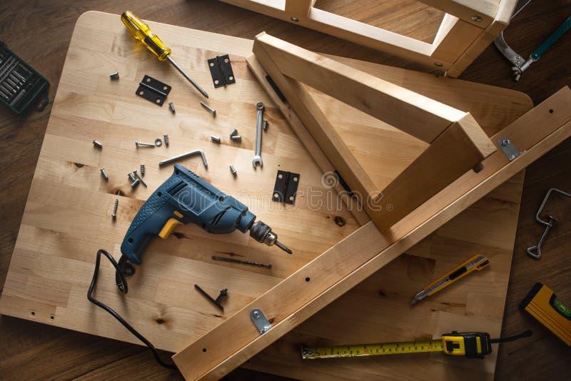 Vista superior de la herramienta del taladro y de otro equipo en los muebles de madera de la tabla asamblea, mejora o reparación  imagen de archivo libre de regalías