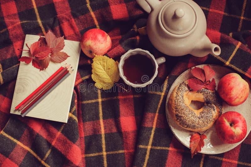 Vista superior de la mañana acogedora del otoño en casa Desayune con el pote del té y del panecillo con las manzanas fotos de archivo