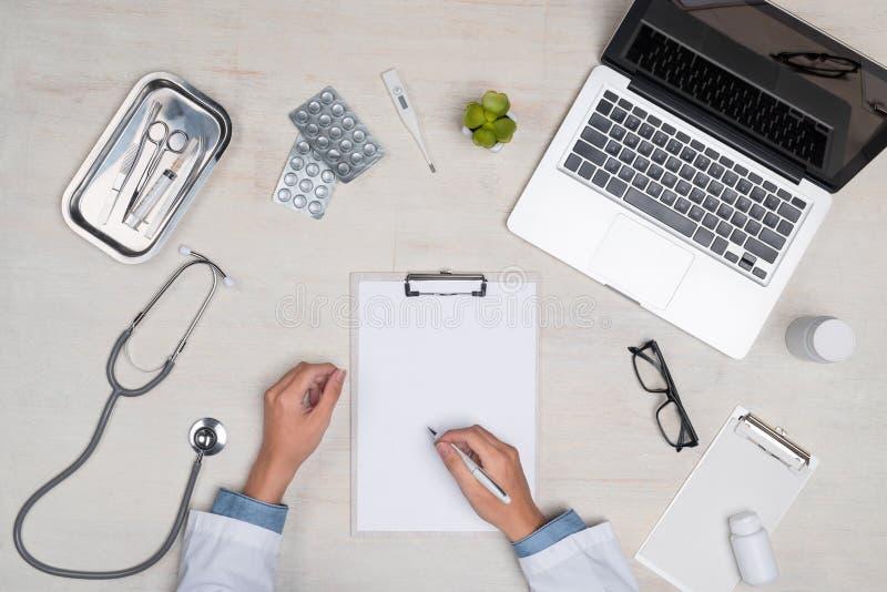 Vista superior de la mano del doctor de la medicina que trabaja en el escritorio foto de archivo libre de regalías